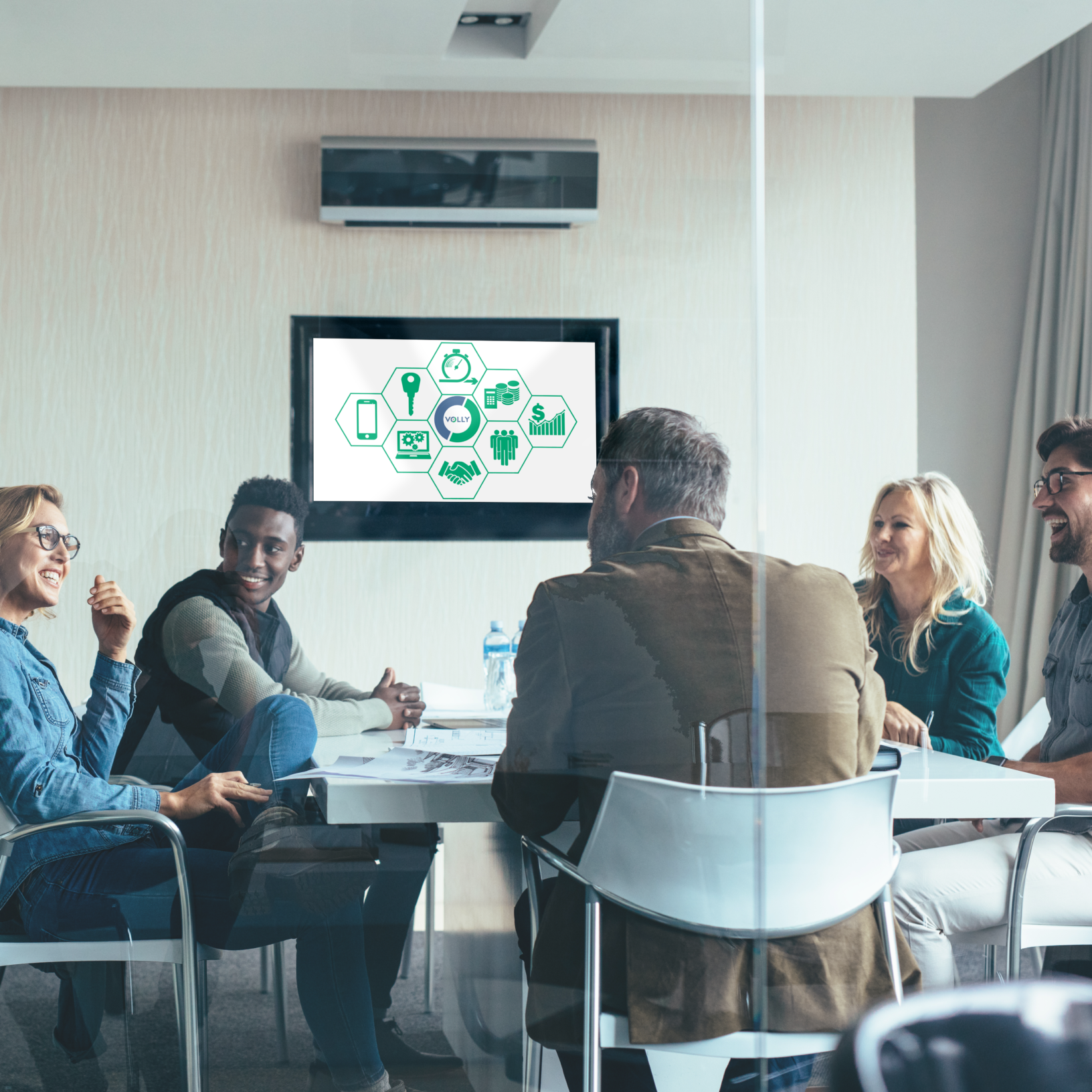A group of people discussing in a meeting, a screen showing the concept on Wholesale with the Volly logo